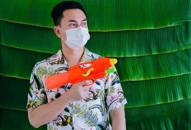 Thailändischer mann, der gesichtsmaske mit wasserpistole für neues normales songkarn-festivalkonzept auf bananenblatthintergrund trägt.