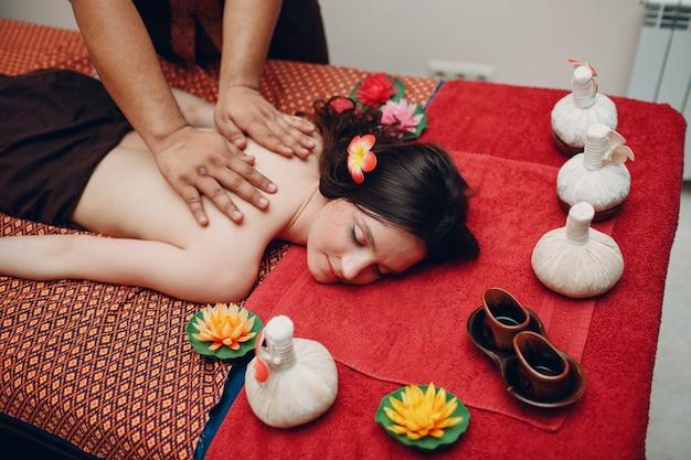 Thailändischer mann, der klassisches thailändisches massageverfahren zur jungen frau am schönheitsbad macht