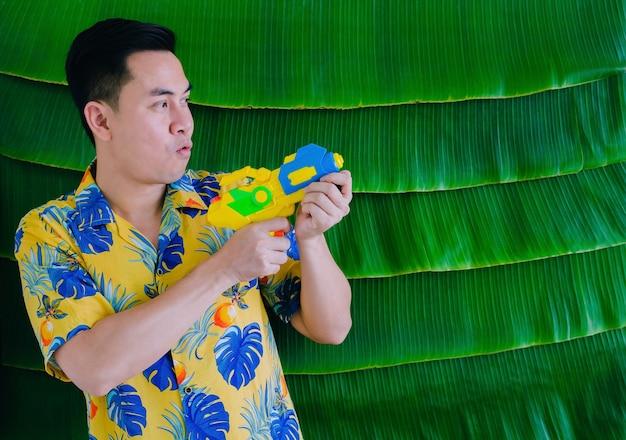 Thailändischer mann, der wasserpistole für songkran festival mit bananenblatthintergrund hält.