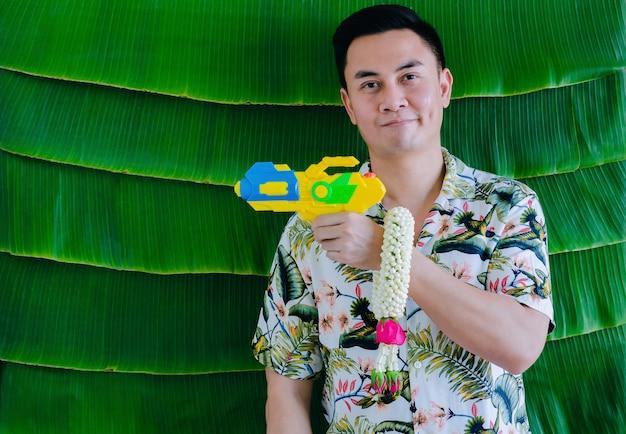 Thailändischer mann, der wasserpistole und jasmingirlande hält, um segen für songkran festival mit bananenblatthintergrund zu geben.