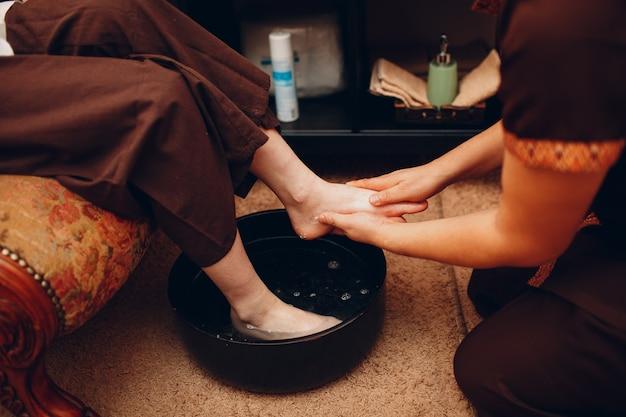 Thailändischer mann wäscht füße beine und macht junge frau im beauty-spa-salon klassische thai-massage