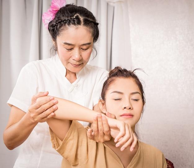 Thailändischer massage-therapeut massiert arm und schulter des jungen mädchens
