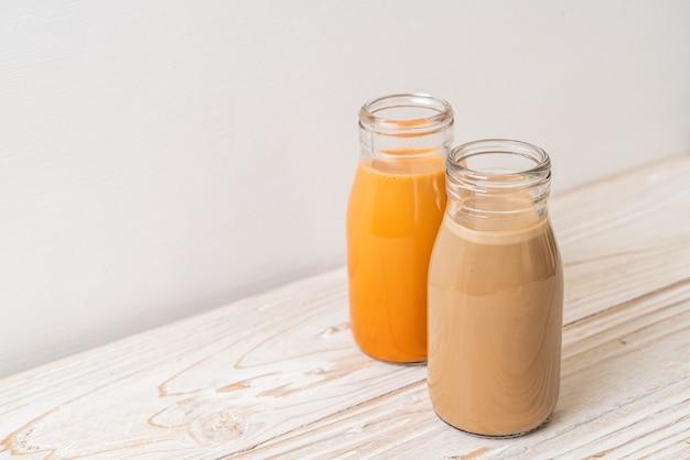 Thailändischer milchtee und kaffee mit milch in der flasche auf holztisch