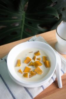 Thailändischer nachtisch: kürbis in der süßen kokosmilch, kokosmilch gedämpfte kürbisschüssel. (buak phak tong)