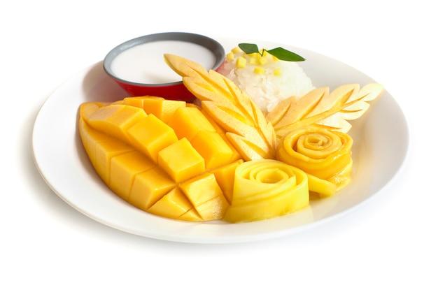 Thailändischer nachtisch, mango mit der seitenansicht der süßen kokosmilch des klebrigen reises lokalisiert auf weißem hintergrund