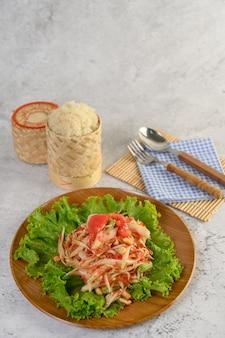 Thailändischer papayasalat in einer hölzernen platte mit tischbesteck