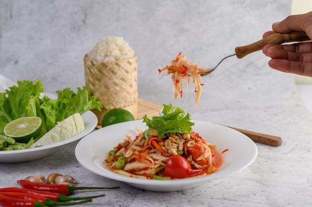 Thailändischer papayasalat in einer weißen platte mit klebrigem reis und getrockneten garnelen