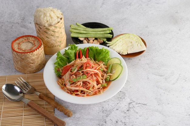 Thailändischer papayasalat in einer weißen platte mit klebrigem reis