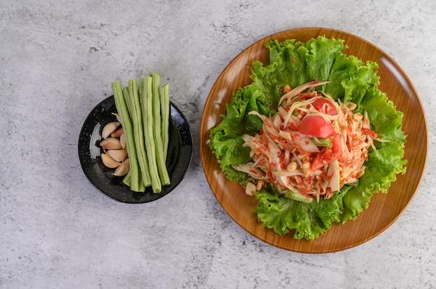 Thailändischer papayasalat in einer weißen platte mit yardlong bohnen, knoblauch und weißem kohl