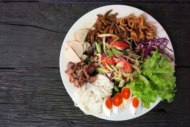 Thailändischer papayasalat oder som tum in der weißen platte auf dem holztisch