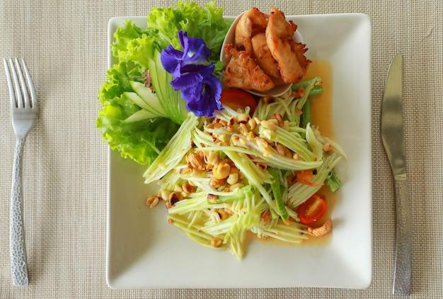 Thailändischer papayasalat scharf und würzig gemischt aus verschiedenen gemüsesorten