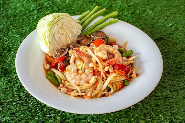 Thailändischer papayasalat wird mit einer garnele und herzmuscheln gemischt.