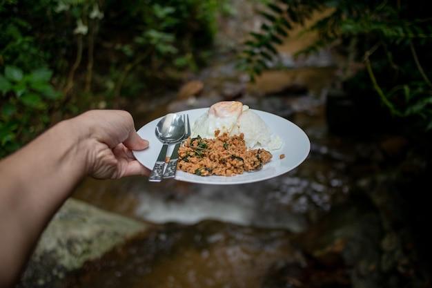 Thailändischer reis gekrönt mit gebratenem schweinefleisch und basilikum mit spiegelei auf flussstrom.