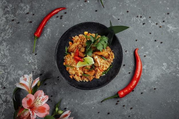 Thailändischer reis mit huhn. thailändisches gericht aus reis, huhn, jalta-zwiebel, mais, ananas, tomate, sojasauce, chilipaste, koriander, limette, chili-pfeffer-gewürzen mit frühlingszwiebeln