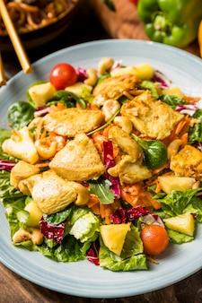 Thailändischer salat mit huhn und gemüse auf keramischer platte