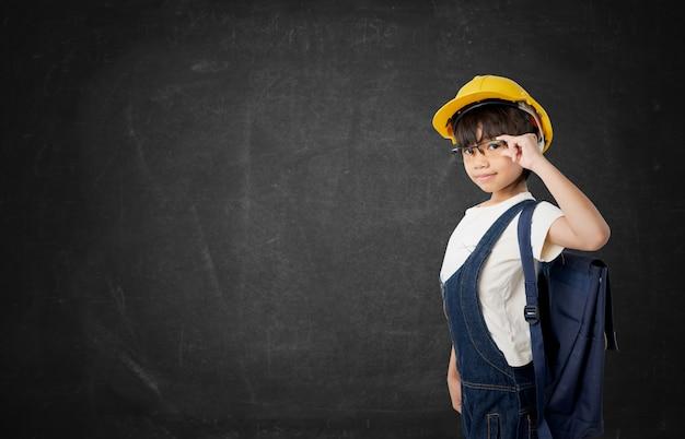Thailändischer student des asiatischen mädchens möchten der ingenieur sein und das kind ausführen, das auf dunkler tafel lokalisiert wird