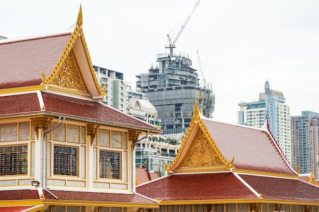 Thailändischer tempel vor dem stadtbau. vertreter zwischen religion und städtischer zivilisation; gebäude und konstruktion sind hintergrund., bangkok, thailand.