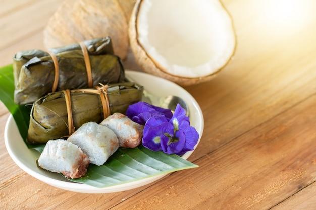 Thailändischer traditioneller dessert-klebreis mit bananen (khao tom mat) auf holztisch