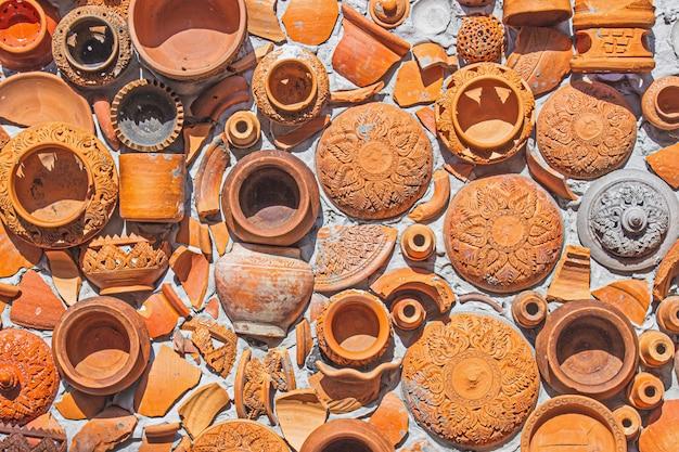 Thailändischer und brauner beschaffenheitshintergrund der nahaufnahme-tonwaren auf wand für innen- oder außendekoration.