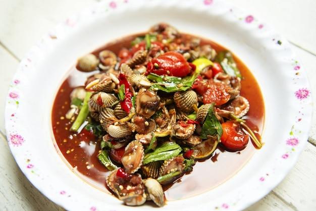 Thailändisches artlebensmittel der scharfen und würzigen schalentierblutherzmuschelsalatmischung gemüsetomatenkraut und der gewürze