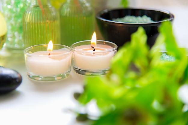 Thailändisches badekurort-behandlungsaromatherapiesalz und naturgrünzucker scheuern sich und felsenmassage mit grüner orchideenblume auf hölzernem weiß mit kerze. thailand. gesundes konzept. kopieren sie platz, wählen sie und weicher fokus