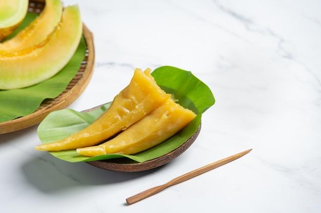 Thailändisches dessert. cantaloupe gedämpftes gebäck auf bananenblatt gelegt