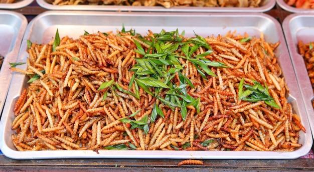 Thailändisches essen am markt. gebratene insektenmehlwürmer als zwischenmahlzeit