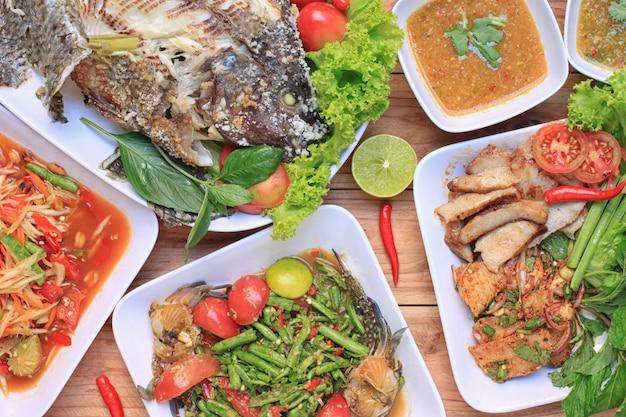 Thailändisches essen auf holzfußboden, papayasalat (som tum), würziger gegrillter schweinefleisch-salat.