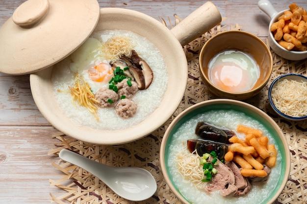 Thailändisches essen frühstücksset weich gekochtes ei und hackfleischbällchen mit reisbrei im tontopf, serviert mit einer weiteren schüssel mit jahrhundertei und geschnittener leber mit knusprigen nudeln