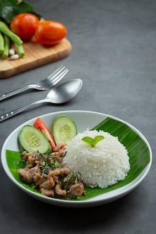 Thailändisches essen, gebratenes schweinefleisch mit kaffirlimettenblättern mit reis servieren