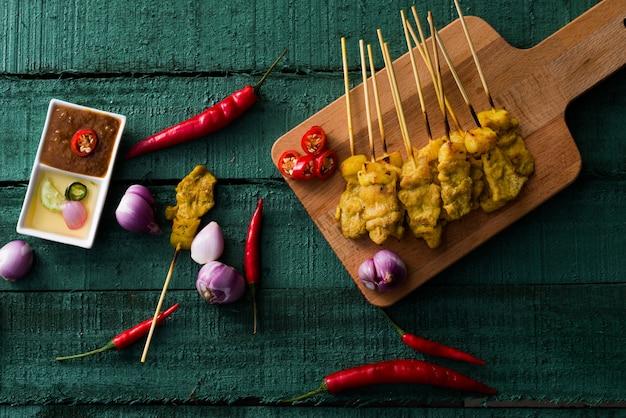 Thailändisches essen, gegrilltes schweinefleisch-satay mit erdnuss-sauce und essig