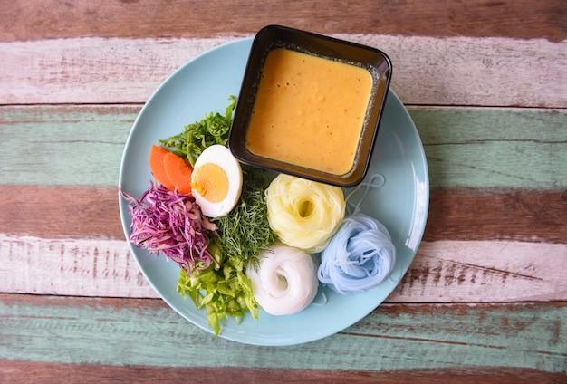Thailändisches essen lecker und schönes essen. reisnudel bunte oder thailändische reisnudeln und fischkrabben-currysuppe mit gemüse auf teller holztisch