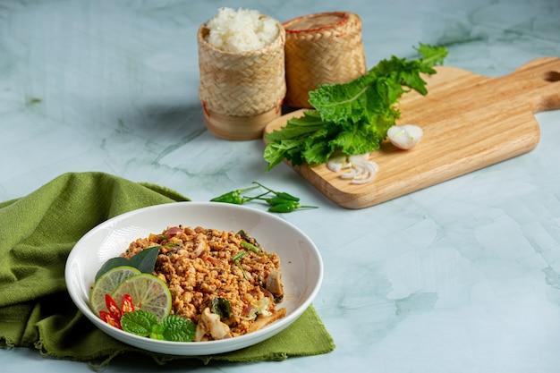 Thailändisches essen mit würzigem gehacktem schweinefleisch, serviert mit beilagen und klebreis