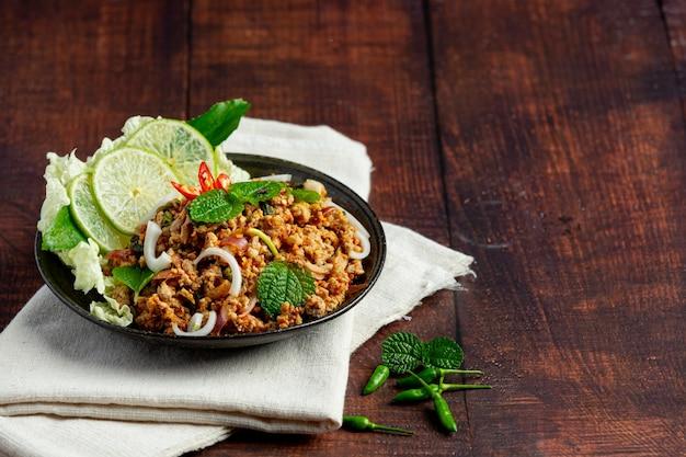 Thailändisches essen mit würzigem gehacktem schweinefleisch, serviert mit beilagen