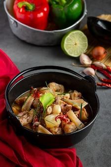 Thailändisches essen mit würziger schweinebeinsuppe in der schwarzen schüssel