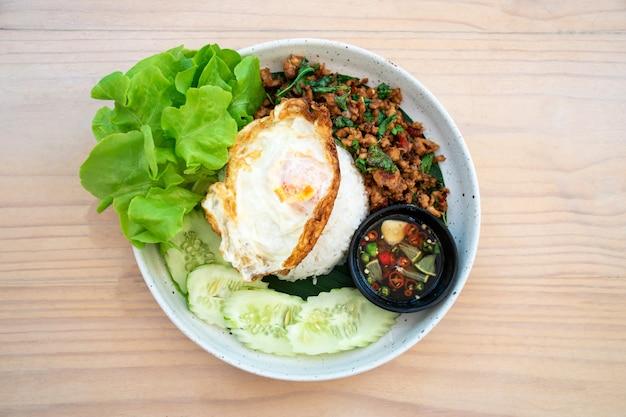 Thailändisches essen, reis mit gebratenem schweinefleischbasilikum auf einem holztisch