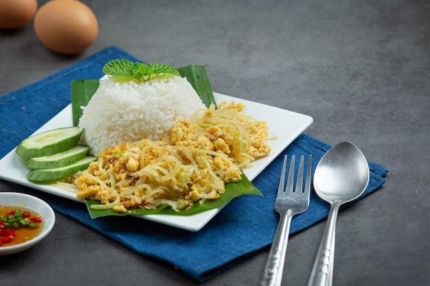 Thailändisches essen spiegelei mit gekochter papaya umrühren, mit reis servieren