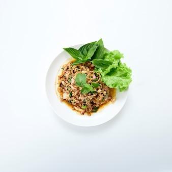 Thailändisches essen würziger gehackter schweinefleischsalat, serviert mit frischem gemüse auf weiß