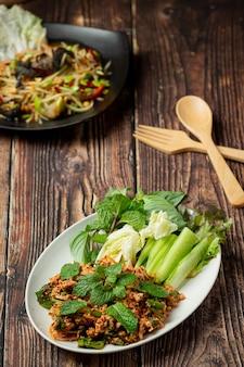 Thailändisches essen, würziges gehacktes schweinefleisch mit beilagen
