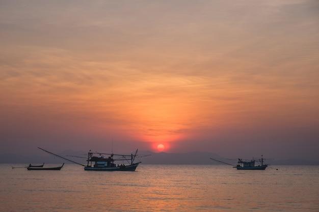 Thailändisches fischerboot in meer während des sonnenuntergangs