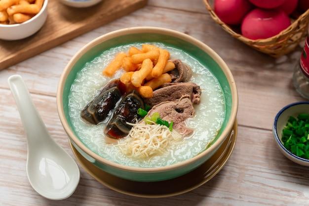 Thailändisches frühstück reisbrei mit jahrhundertei und gekochtem fluss serviert auf holzoberfläche