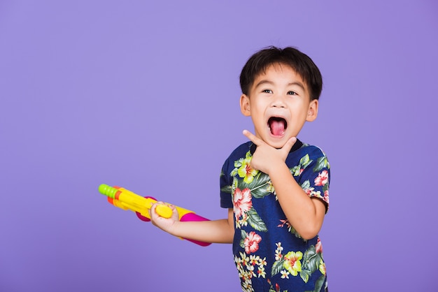 Thailändisches kind lustig halten spielzeug wasserpistole und lächelnd, glücklicher asiatischer kleiner junge, der plastikwasserpistole hält