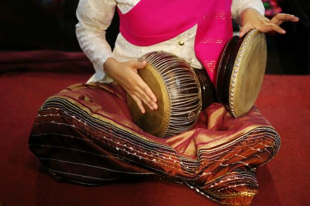 Thailändisches kleid, das thailändische trommel spielt