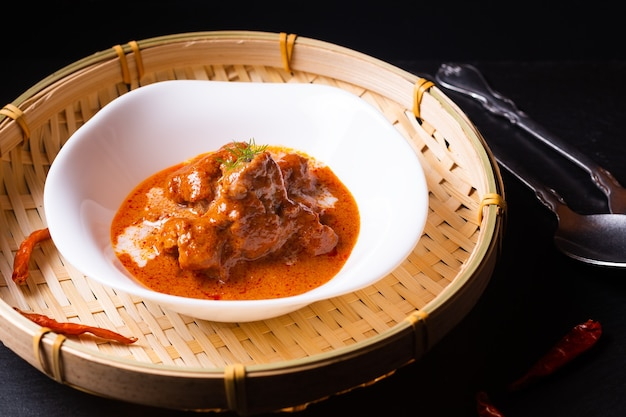 Thailändisches küchenkonzept hausgemachtes rotes currykalbfleisch panang in schwarzem hintergrund mit kopierraum