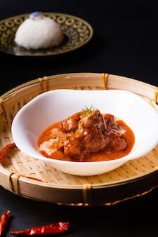 Thailändisches küchenkonzept hausgemachtes rotes currykalbfleisch panang und thailändischer reis auf schwarzem hintergrund mit kopierraum