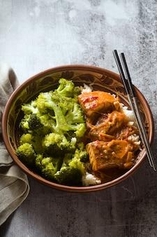 Thailändisches lachsgericht in kokosnusssauce mit frischem brokkoli und reis in einer tonschale mit stäbchen