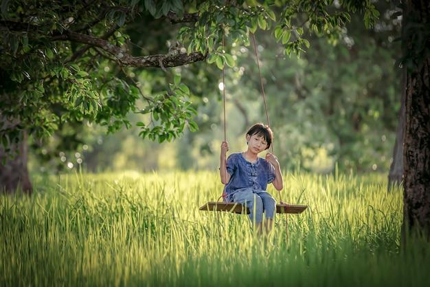 Thailändisches landwirtmädchen, das auf einem reisgebiet lebt