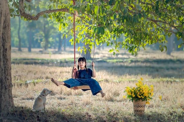 Thailändisches landwirtmädchen, das schwingen mit ihrem welpen spielt