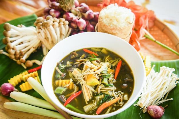 Thailändisches lebensmittel der bambussprosssuppen- und -pilzkräuter- und -gewürzbestandteile diente auf tabelle mit klebrigem reis.