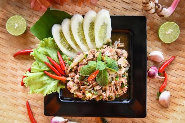 Thailändisches lebensmittel des würzigen gehackten schweinefleischsalats diente auf behälter mit kräutern und gewürzbestandteilen